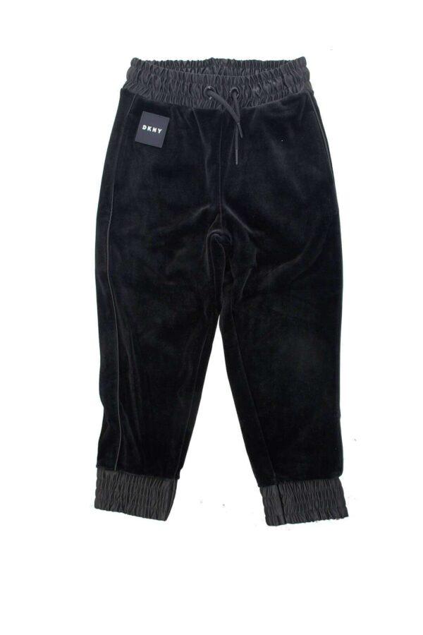 Scopri il nuovo pantalone da bambina firmato dalla collection DKNY. Il tessuto in ciniglia è impreziosito dal piping laterale e dalla vita e i polsi elastici. Lusso e comodità in un solo capo.