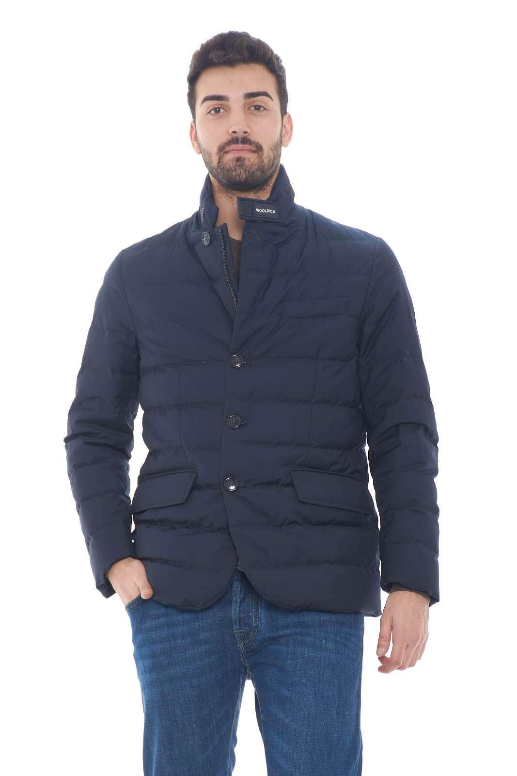 Un piumino dal modello blazer quello firmato dalla collezione autunno inverno di Woolrich.  Caratterizzato dal collo alto e la doppia chiusura con zip e bottoni, esalta la linea con i due spacchi sul retro e con le tasche sul davanti a simulare una giacca.  Comodo e versatile, è perfetto per gli outfit formali.