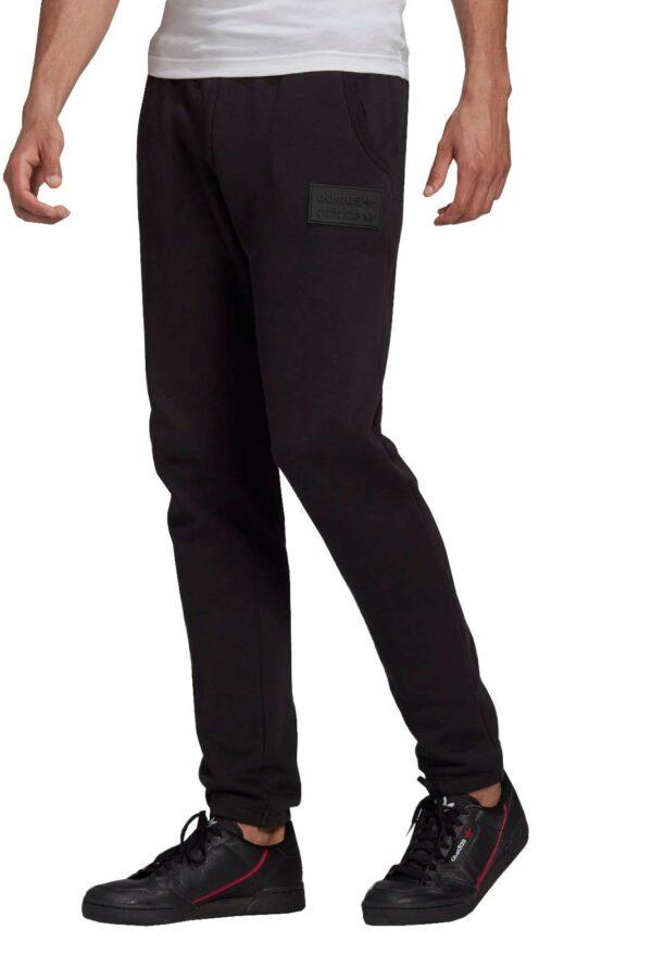 Un pantalone sportivo quello proposto dalla collezione uomo Adidas. Caratterizzato dallo stemma in silicone che gli da un tocco di stile, mentre gli orli elasticizzati ti permettono di far risaltare le tue sneaker.